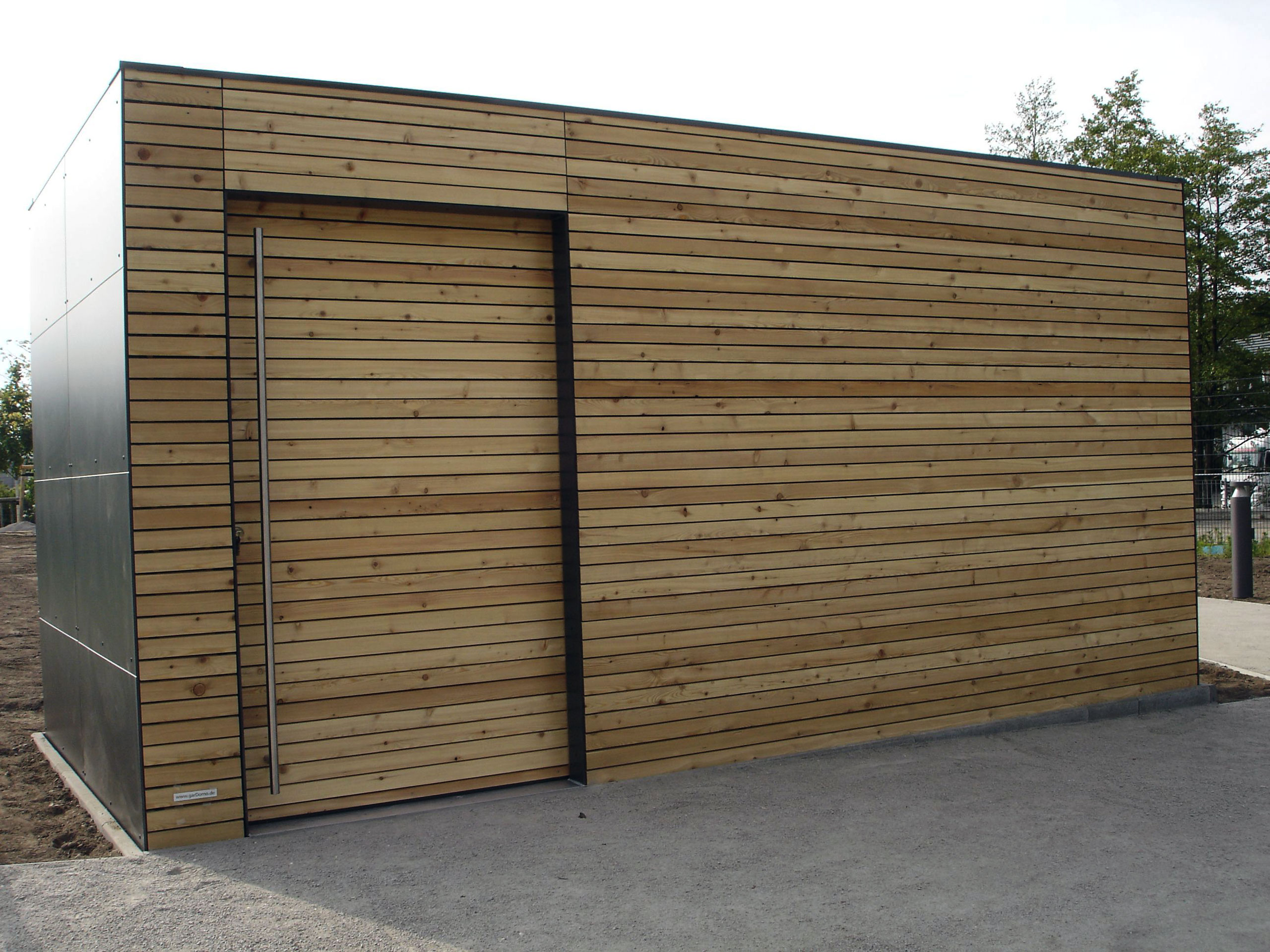 Lamellenfassade in Kombination mit TRESPA®️- ein sehr edles CUBE – Design Gartenhaus an der Elbe